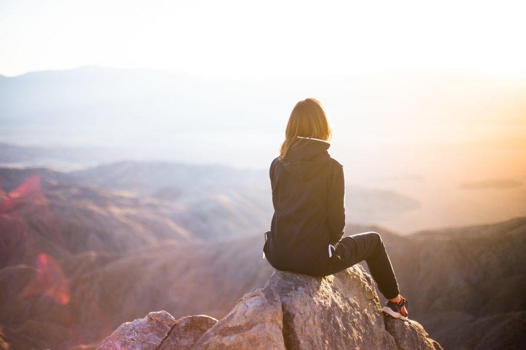 Frau sitzt in der Natur und träumt